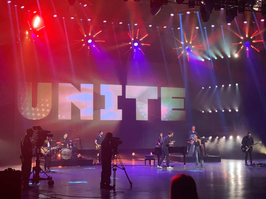 an image of the Unite to Fight Poverty concert shows band members and camera people on a large stage with bright red and purple lights all around them and the word Unite on the wall behind the stage
