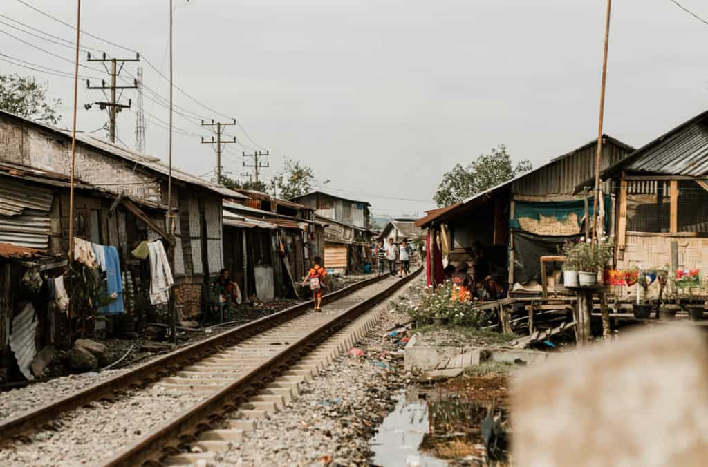 View of a child, wearing a backpack and orange shirt, walking away down a train track with extreme living conditions, impoverished homes lining the tracks in a slum neighborhood.