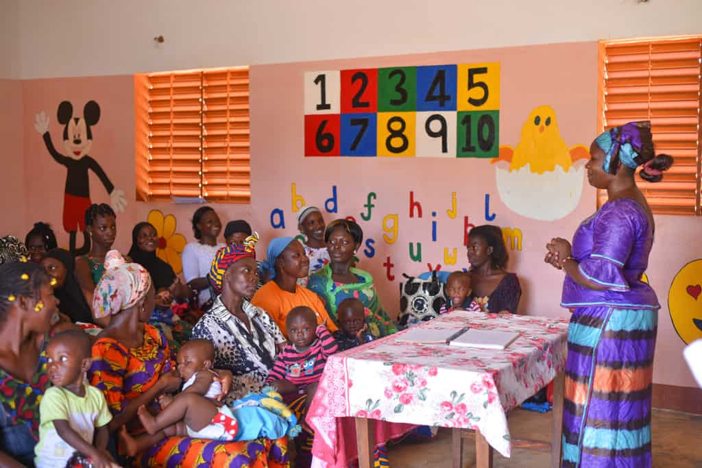 Woman talking with a group of mothers with young children in a children's classroom.