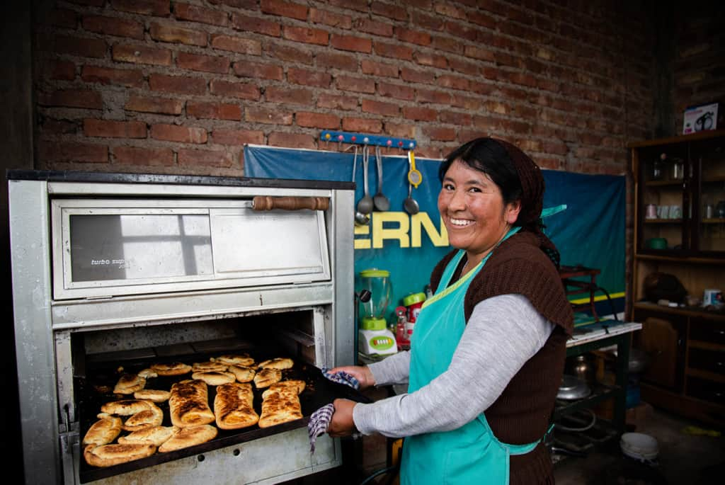 Woman wearing a brown and gray shirt and a green apron. She is taking a pan of her baked goods out of the oven. The background is a brick wall.