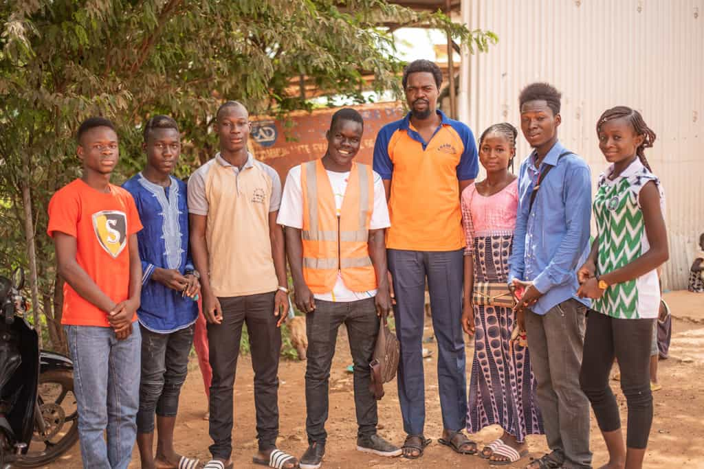 Nourou is standing with his teacher Jean Baptiste Nacanabo and his classmates at the Compassion project.