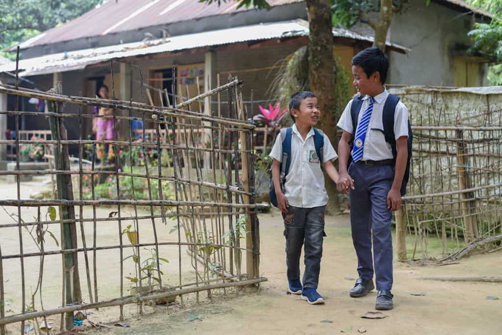 Two boys walk out of a fence. They are wearing white shirts and backpacks, ready for school
