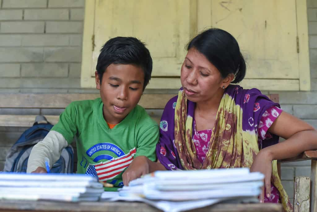 a boy wearing a green shirt and his mother, wearing a colorful purple and yellow outfit, look over school papers, homework.
