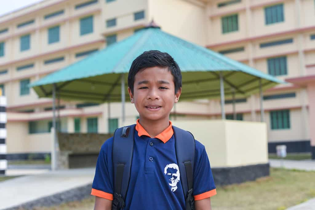 a boy wearing a blue and orange shirt smiles at the camera.