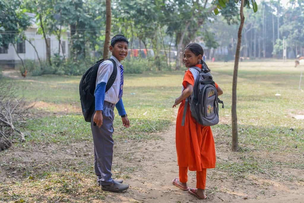 a boy and girl, brother and sister, walk down a dirt path wearing backpacks, heading for school