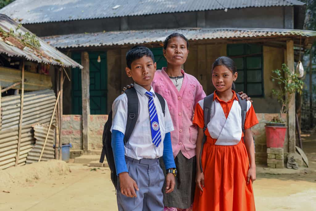 a mother wearing a pink shirt stands behind a boy and girl, each wearing a backpack. The boy wears a white shirt and blue tie. the girl wears an orange and white dress