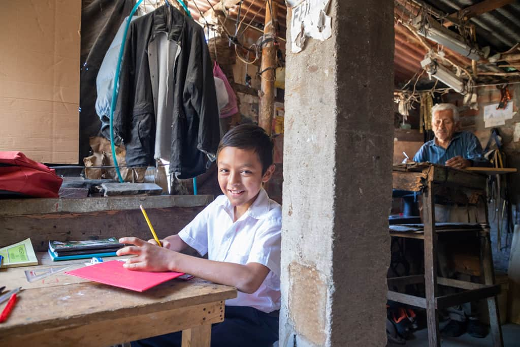 A boy wearing a white shirt sits at a wooden desk in his home school. He has school supplies in front of him on the table. A man works at a separate desk in the background.