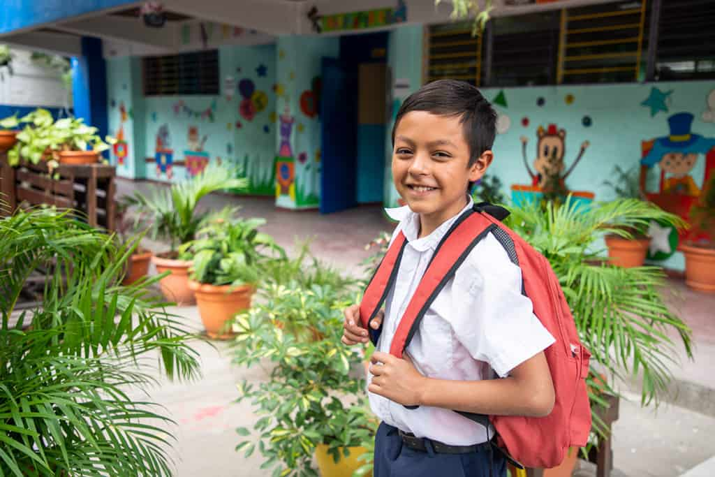 A boy wearing a white shirt and red-orange backpack smiles at the camera and looks ready for school. He is outside of a brightly colored building with many potted plants around him.