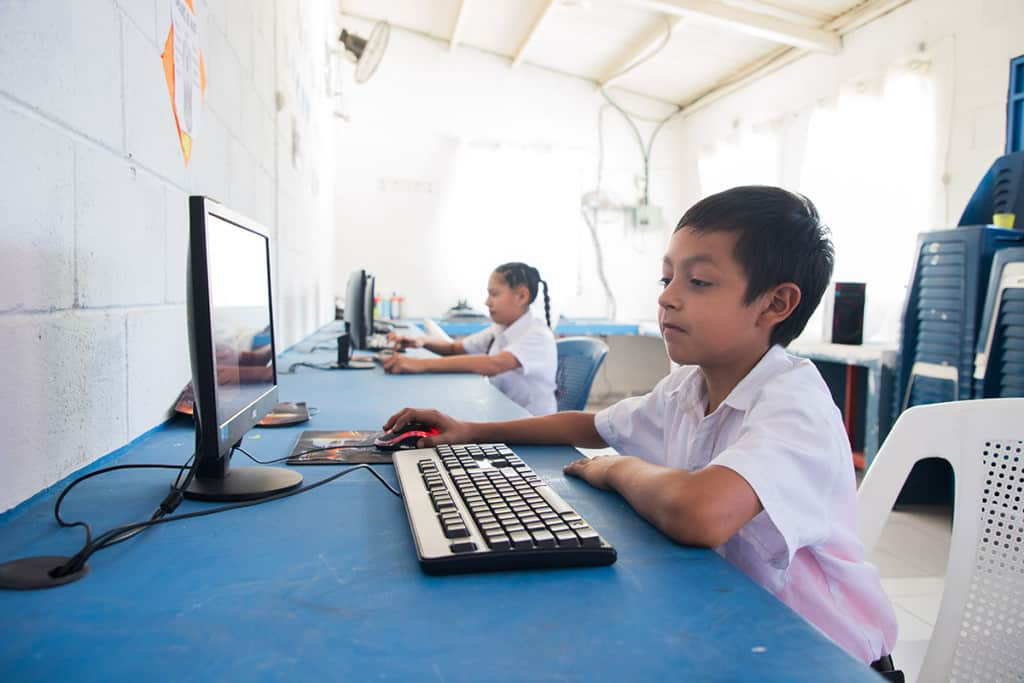 A young boy wearing a white shirt works on a computer. Another child works on a computer nearby. The computers are on a blue table.