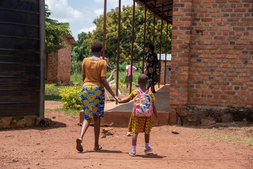 a mother and daughter dressed in brightly colored clothing walk hand in hand on a dirt road.