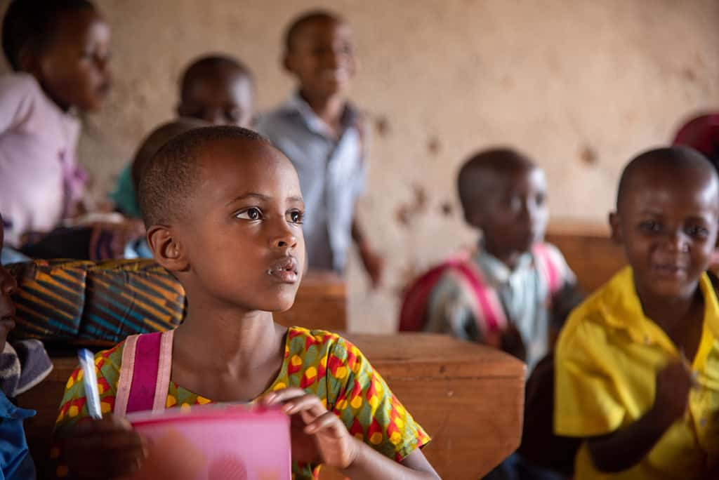 a girl in a classroom with other children has an attentive expression