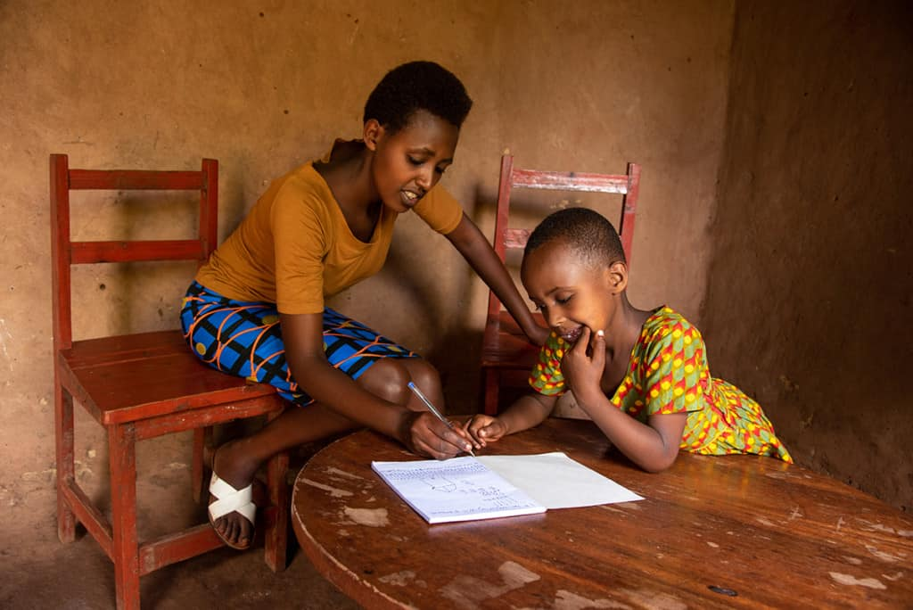 A woman and a young girl lean over papers on a wooden table. The mother is sitting on a wooden chair, and the girl concentrates on the papers, home school work.