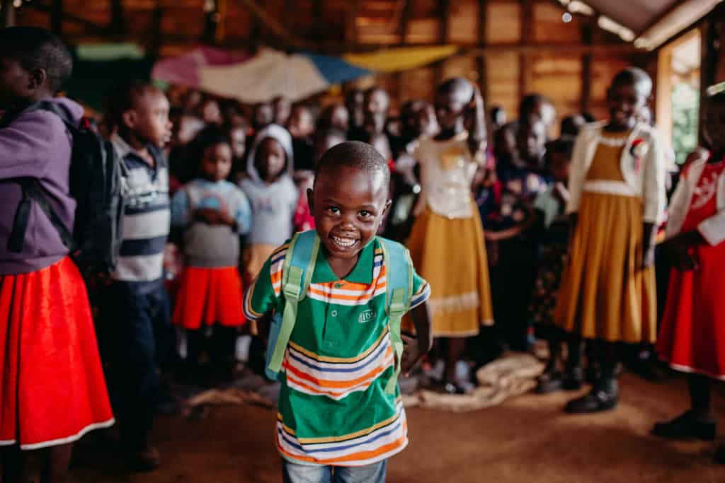 A young boy smiles while wearing a new backpack he got at a Compassion Christmas celebration. Children are standing behind him