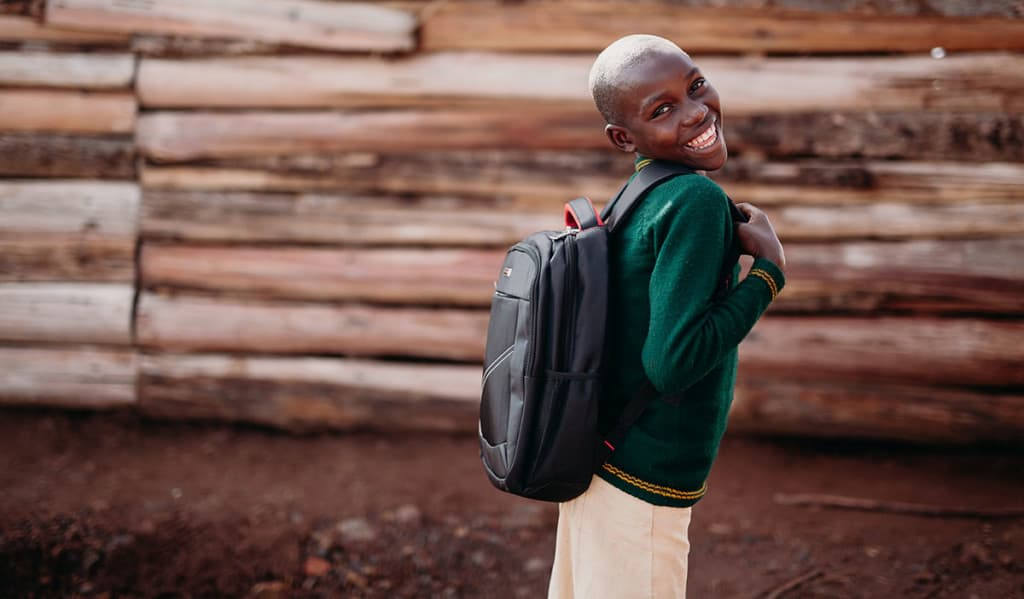 a girl wearing a green sweater smiles while wearing the new backpack she got at the Compassion Christmas celebration