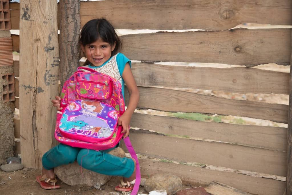 A 5-year-old girl with a shy expression holds a large pink backpack. She is wearing teal and white clothing. A wooden wall is behind her.