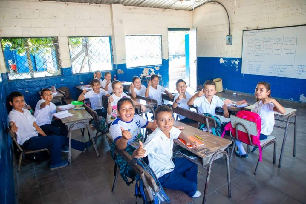 Students in El Salvador give thumbs up signs from their school classroom