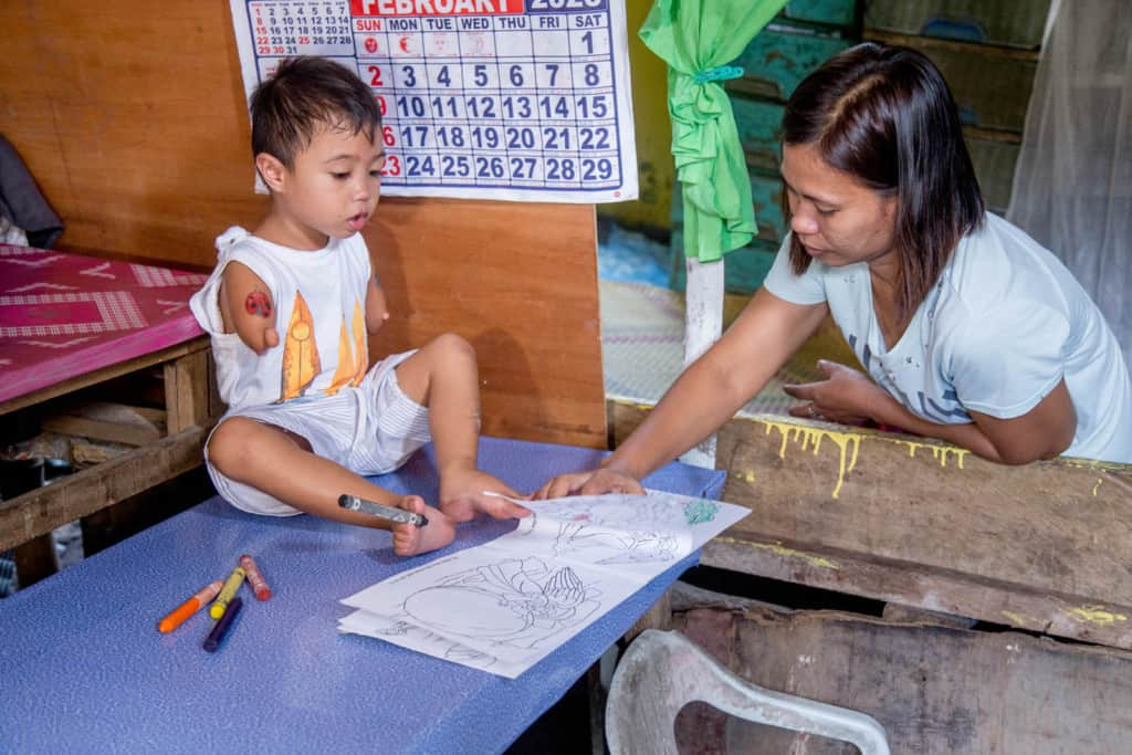 Jasper is sitting on a blue table using his feet to color in a coloring book. His mother, wearing a white shirt, is standing beside him. Jasper is wearing a white shirt and gray and white striped shorts. There is a calendar on the wall behind him.