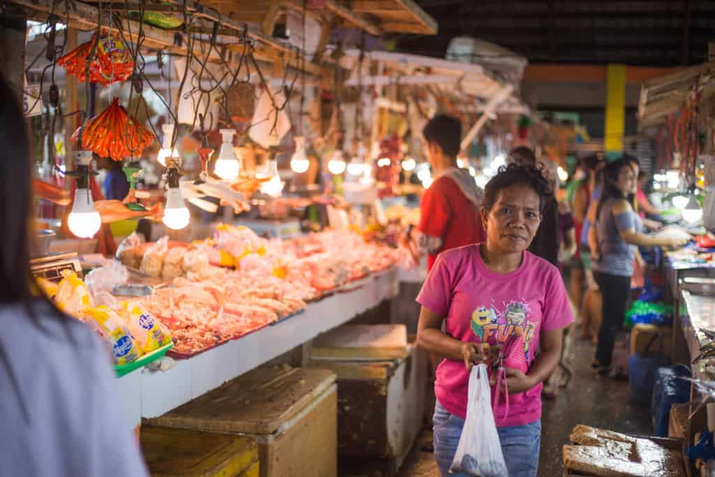Woman wearing a pink shirt and is at the market near a milkfish stand. There are lights above the table.