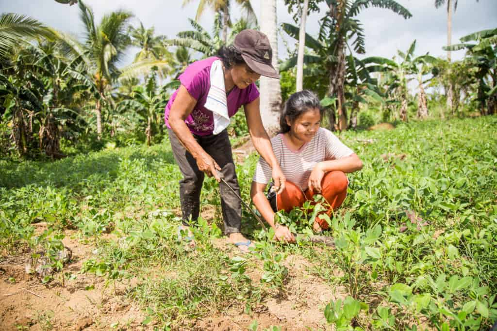 Joan and her mother, Marlyn, are working together in a field. Joan is wearing red pants and a pink and white striped shirt. Marlyn is wearing a purple shirt and gray pants.