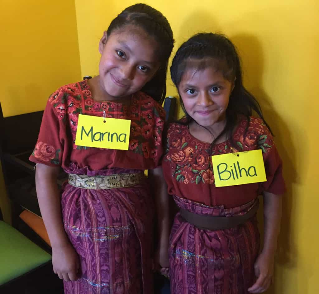 Two young girls, sisters, wearing traditional Guatemalan clothing of skirts and floral blouses. They are smiling.