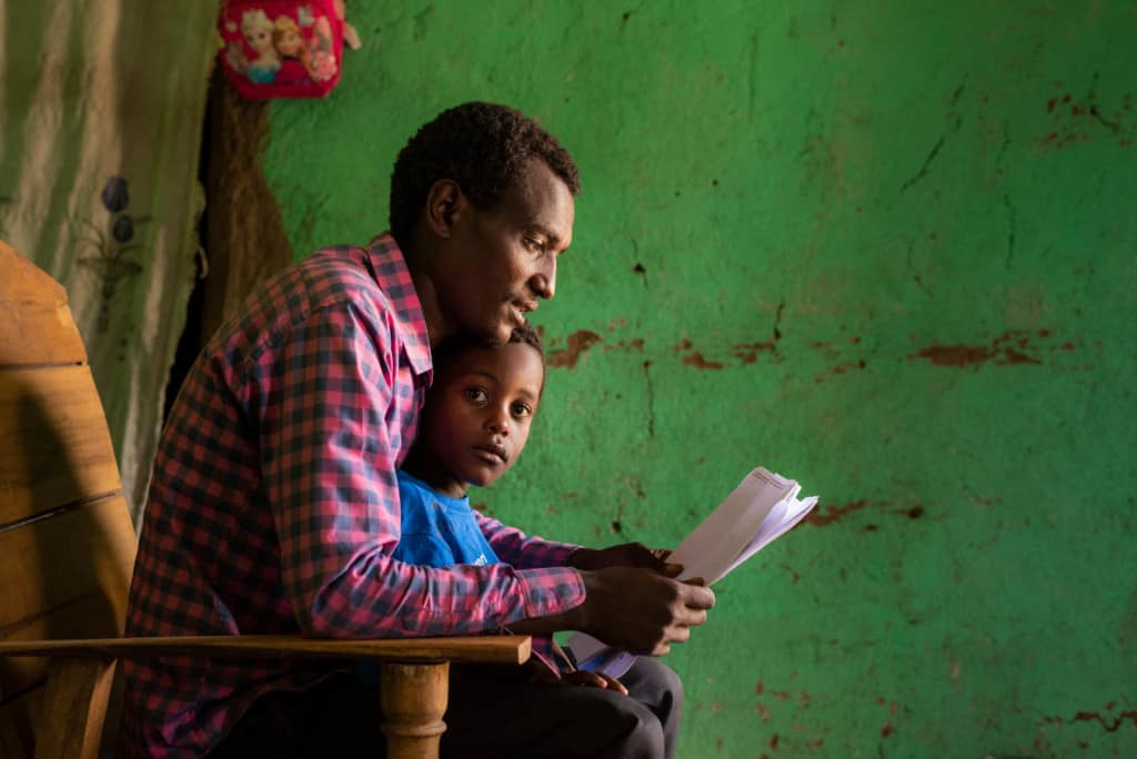Kenenisa is wearing a blue shirt. He is sitting on his father's lap while his father reads his sponsor's letter to him. Kedir is wearing a red and black checked shirt. The wall behind them is green.