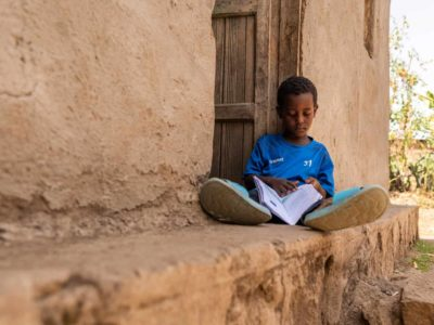 Kenenisa is wearing a blue shirt. He is sitting on a small ledge by the front door of his house and is looking through his sponsor's letters. His house is tan.