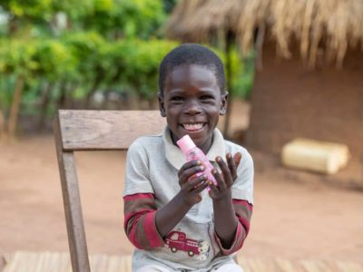 young boy with a huge smile sitting