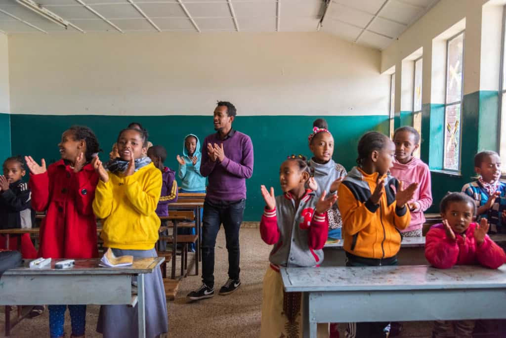Teacher wearing a purple sweater and black pants. He is standing in a Compassion classroom with a group of children. They are all singing and clapping their hands together.