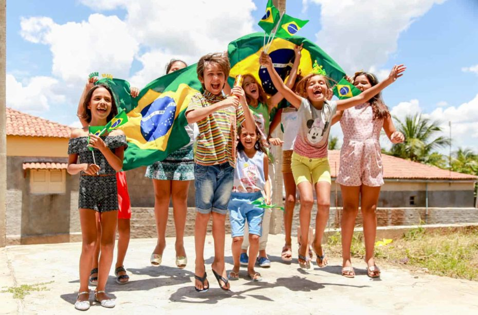 A group of children in Jericó, Brazil, cheer and laugh holding Brazilian flags. Some children are jumping, dancing.