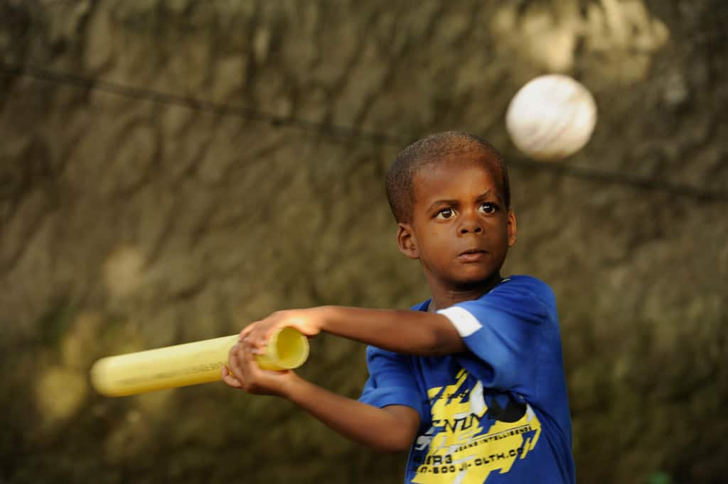 Boy swings a bat outside in his yard near his home, keeping his eyes concentrated on the white ball. He is wearing a blue shirt.