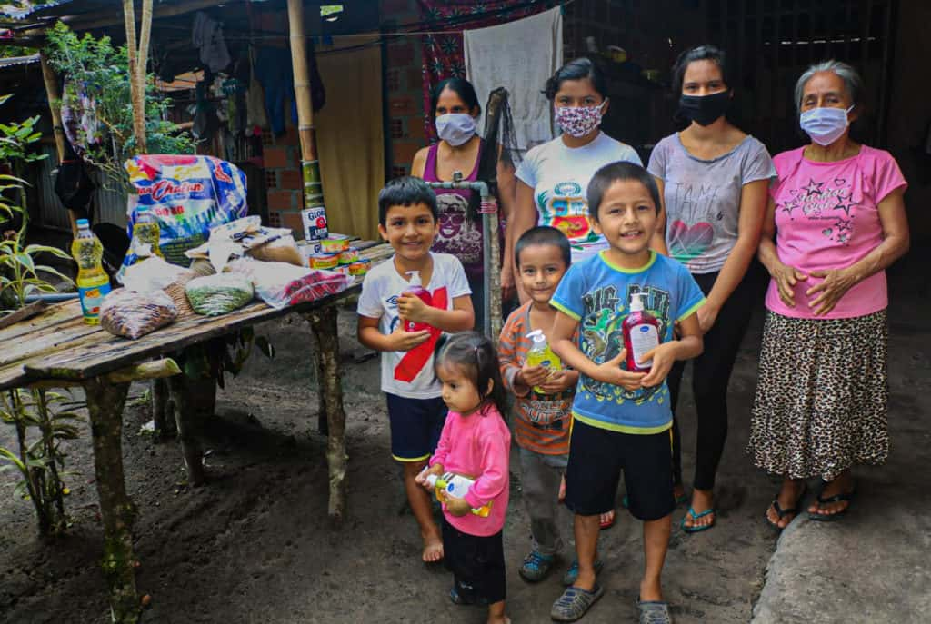 Children standing and holding some supplies. Adults are standing behind the boys and next to the food brought by the Compassion center. The girls are all wearing face masks. They are all outside their home.
