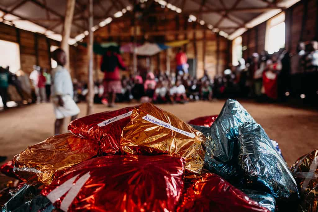 a pile of presents in shiny wrapping paper is seen in the foreground, while children sit in the background inside the barnhouse church