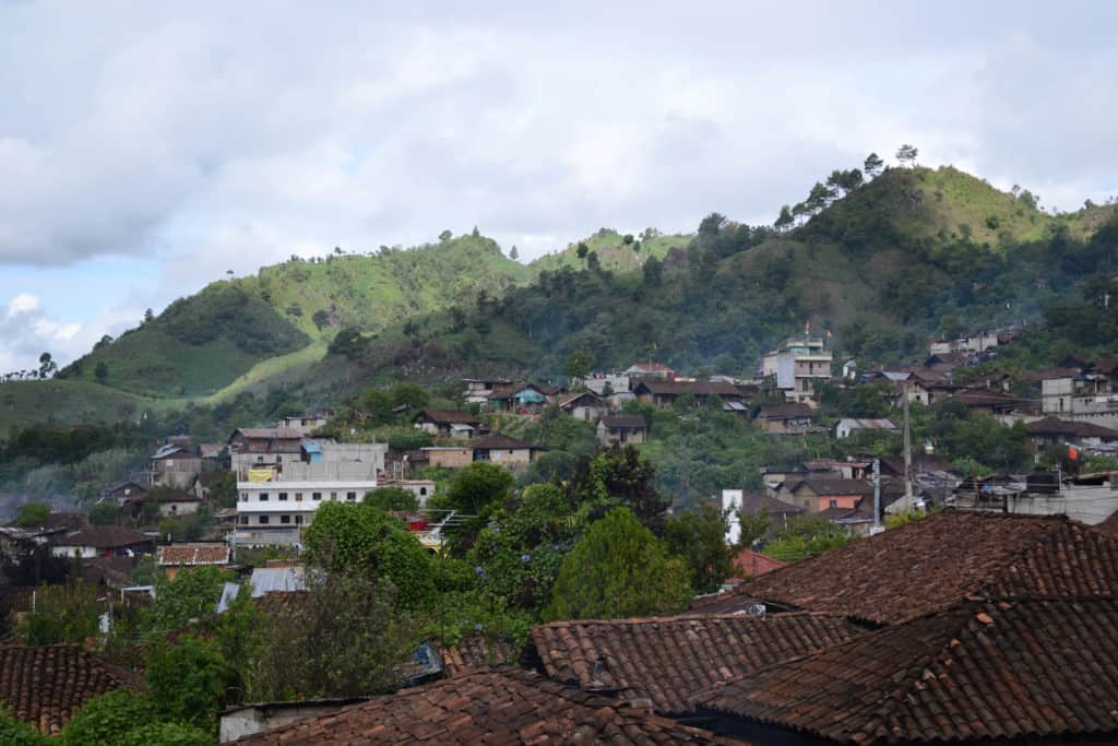 View of rolling hills with green trees and forest in the region of the Highlands showing the village of Chajul, Quiche.