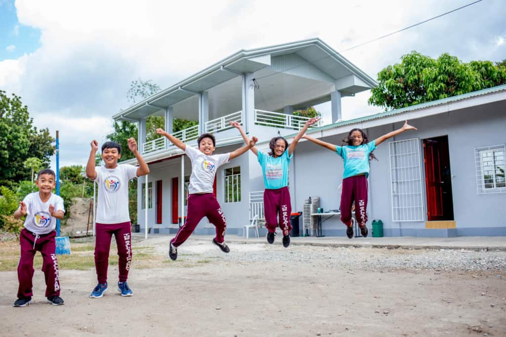Children jumping and laughing in front of the child development center buildings, which are white with red doors. The boys are wearing white uniform shirts and the girls are wearing blue, turquoise.