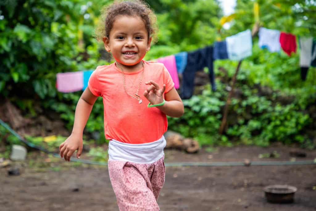 Little girl running outside her house. She is wearing an orange shirt and a pink skirt. Behind her are clothes hanging on a clothesline.