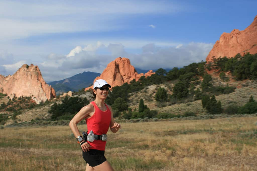 A woman smiles while running in a wilderness area. Behind her are jagged red rocks, blue sky and mountains. She is wearing a white hat, red shirt and black shorts, plus some running accessories.