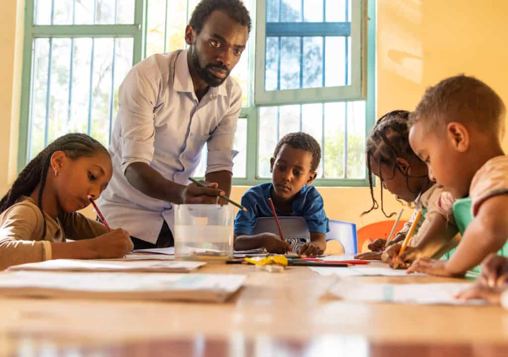Kenenisa is wearing a blue shirt. He is sitting around a large table in a classroom with yellow walls. He and several other children are writing letters to their sponsors and drawing pictures for them. The children are using colored pencils. The project's social worker, Misgana, wearing a white shirt, is helping the children.