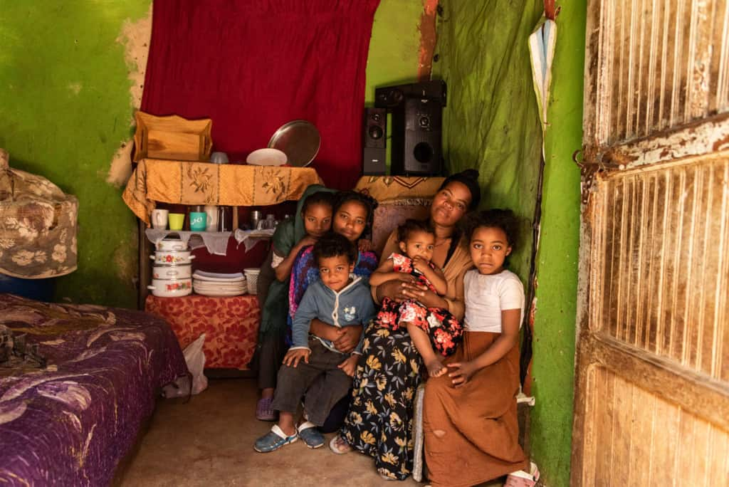 Mother wearing a tan sweater and a black floral skirt. She is sitting in her home surrounded by her children.