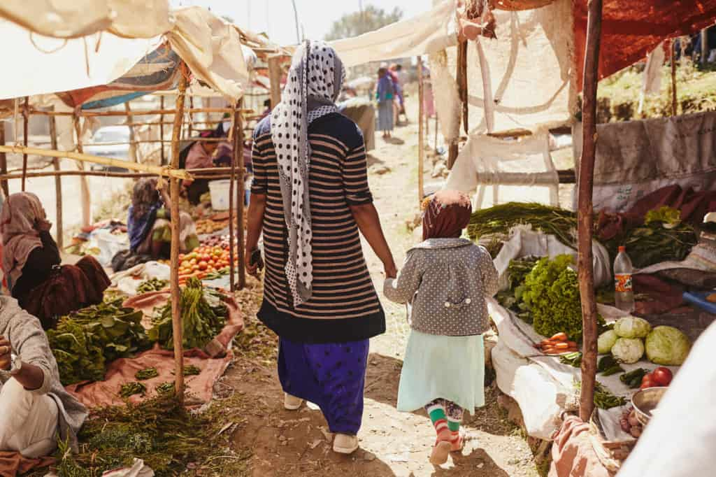 Mother, in a blue skirt, and her daughter, in a brown head covering, hold hands as they walk through the market where the mother makes a living selling vegetables. There are stalls with women sitting on the ground surrounded by produce. The stalls are covered by tarps, fabric.