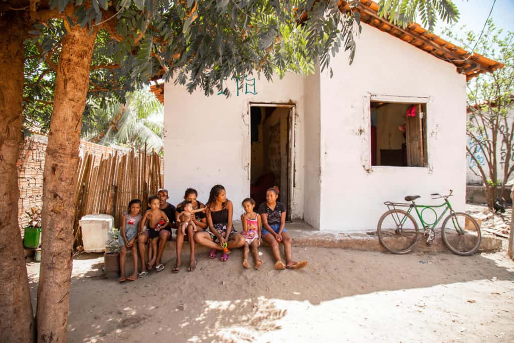 Ana Maria and her family are sitting in front of their home. The house is white. To the right is a green bicycle and there are trees on the left.