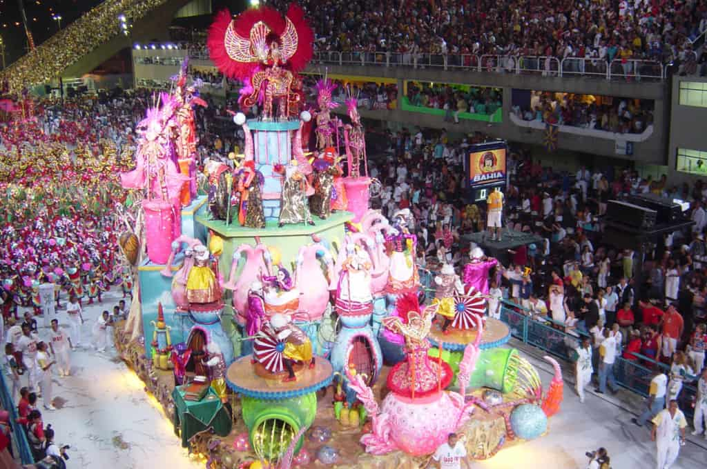 Colorful parade float surrounded by a large crowd of spectators.