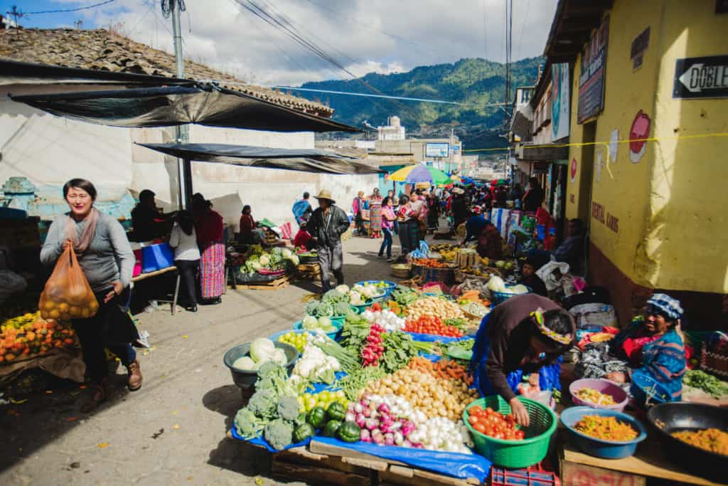 Vegetables are on blue tarps at a street market in Cantel. A woman in a gray shirt walking on the street carries an orange bag full of produce. Another woman leans over a green plastic basket full of tomatoes next to a yellow building. There are hills and more people in the background.