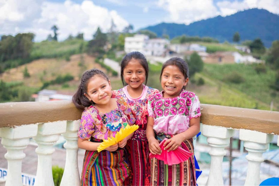 Three girls standing together and smiling, holding yellow and pink handmade paper fans. They are wearing pink shirts and striped skirts. They are leaning against a railing with white pillars. In the background are white buildings and a green hill.