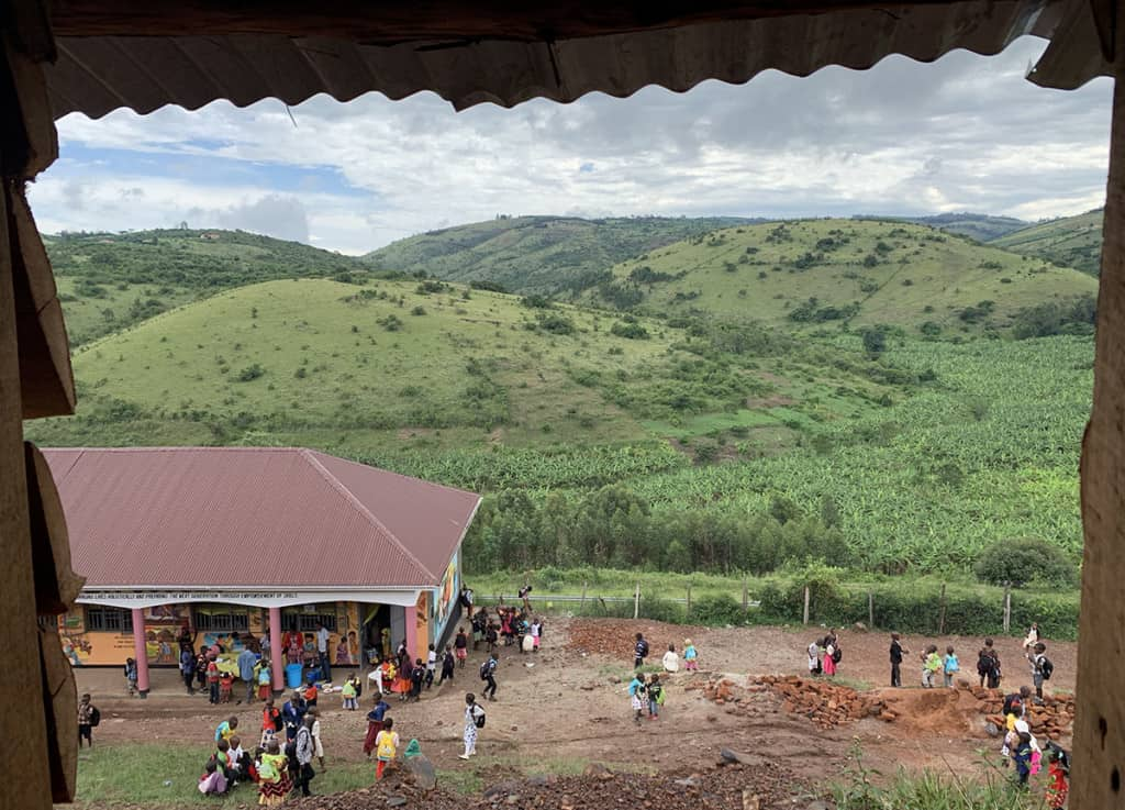 an aerial view of a building surrounded by children, in the background are green hills and a cloudy sky