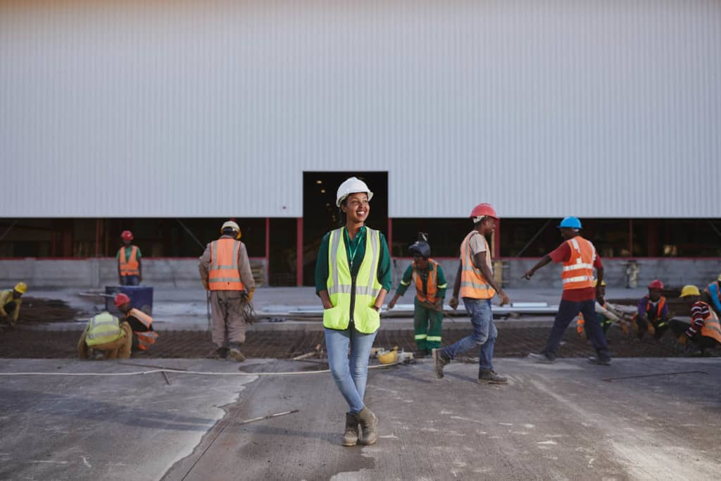Young woman, in a yellow and gray safety vest, green shirt, blue jeans and white hard hat, is at the plant. She is standing on concrete in front of a large white building. There are workers in orange vests in the background.