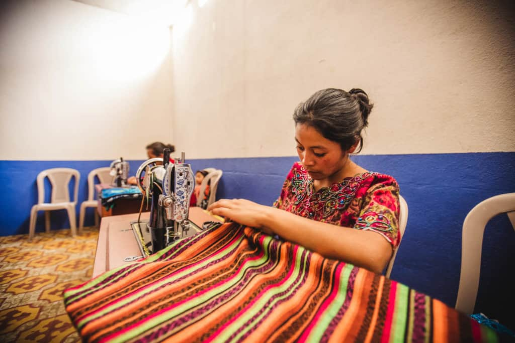A woman in a red shirt sits in a white chair at a black sewing machine working on a striped piece of fabric that is brown, green, orange and pink. The walls in the room are blue and white.