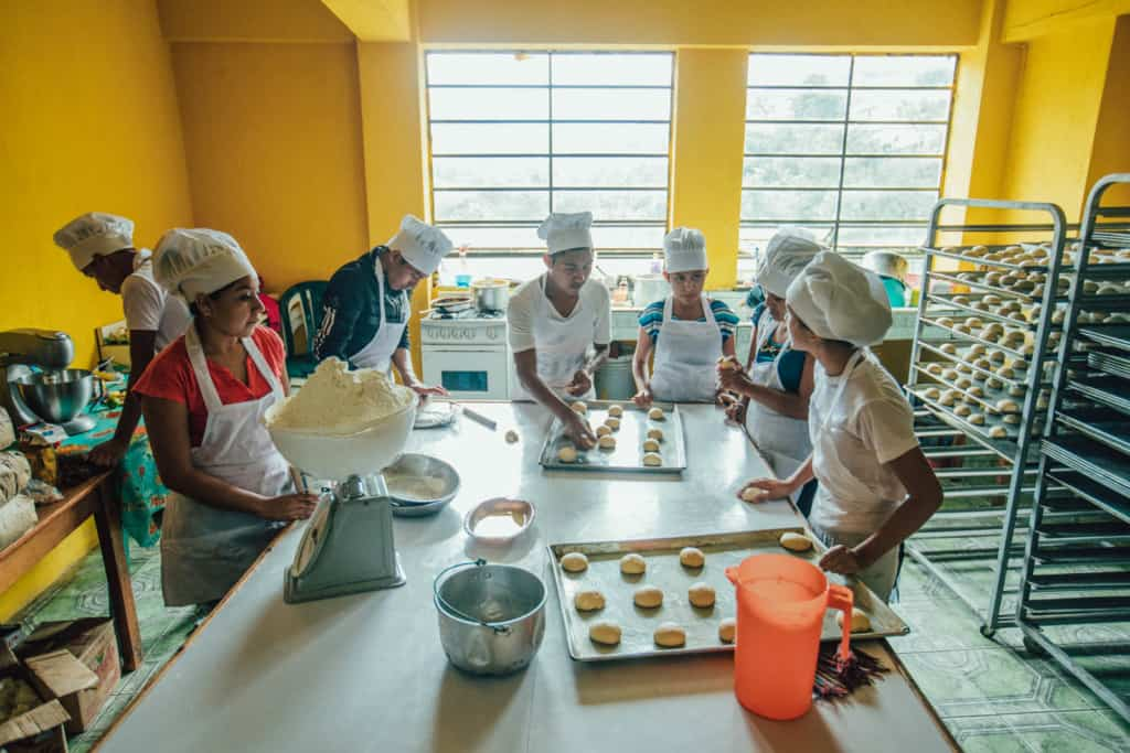 Boys and girls in white aprons and chef hats stand around a white table, counter putting rolls, buns, baked goods onto baking sheets. There is a scale with a bowl of flower on the table. The walls are bright orange, yellow. There are baking sheet racks on one side of the room.