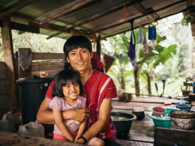 A smiling father in Thailand puts a protective arm around his young daughter, who is wearing a pink shirt and smiling