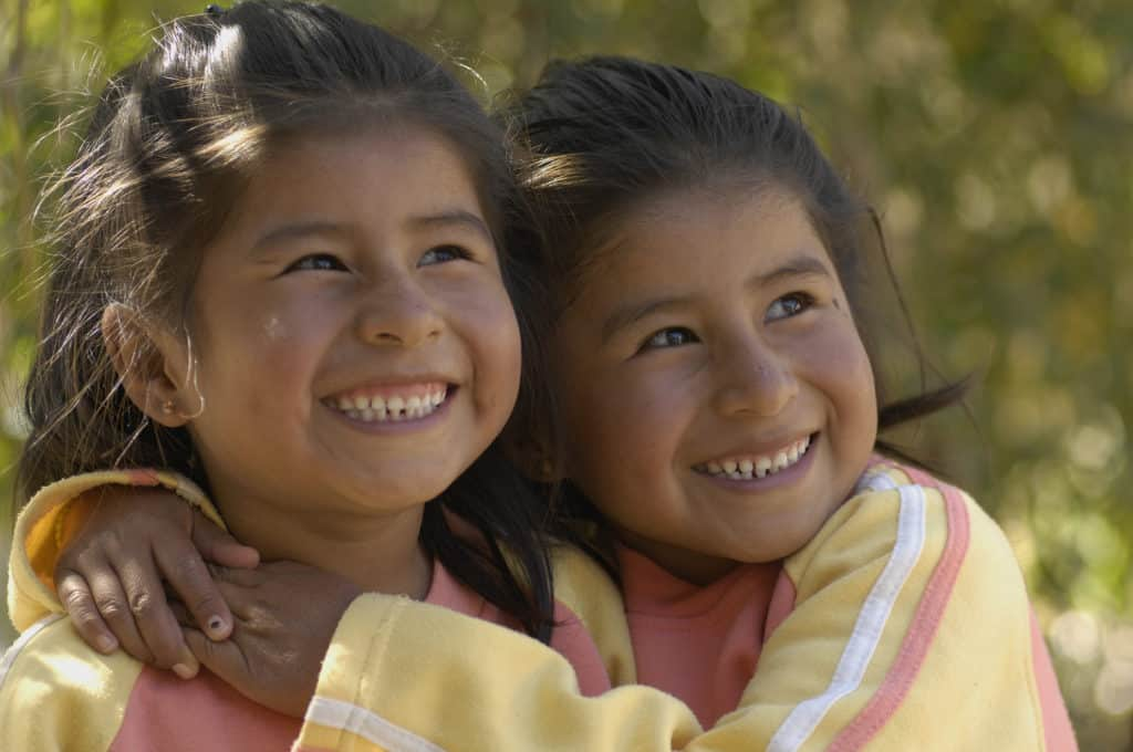 Two identical twin sisters in Bolivia hug each other and smile