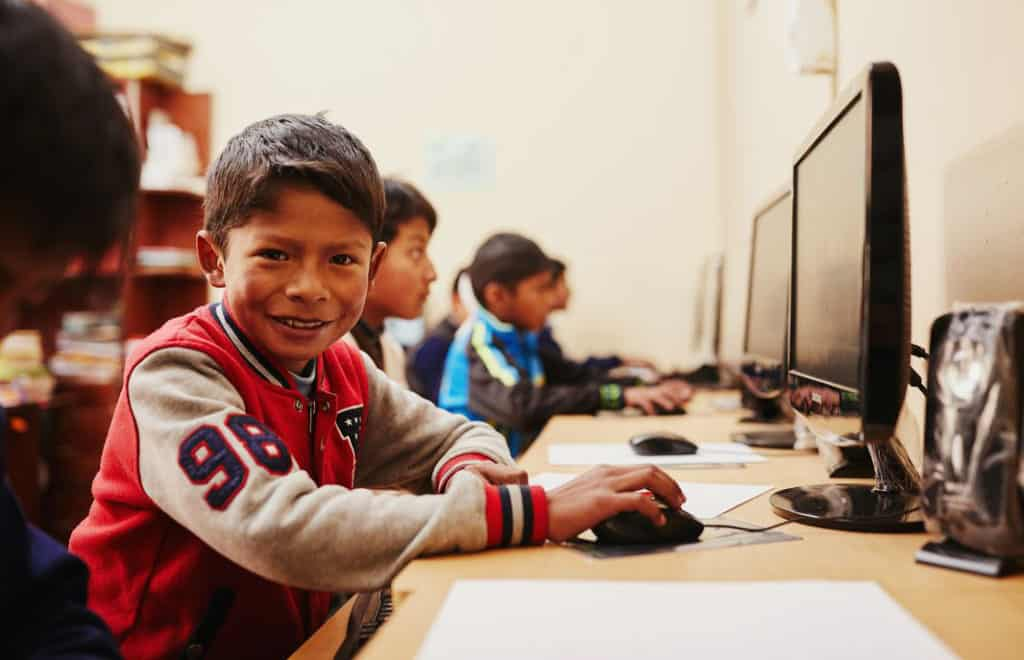 A boy wearing a red and gray jacket with a number patch on the sleeve smiles as he sits in front of a computer. Other children sit at computers nearby.